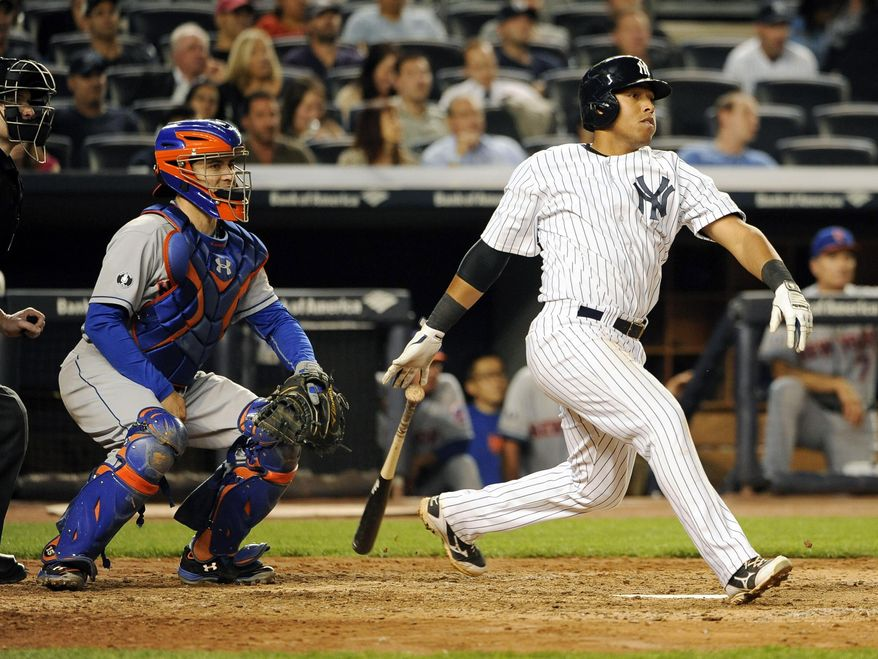 New York Mets catcher Travis d'Arnaud, left, watches New York Yankees' Yangervis Solarte hit an RBI single off of New York Mets starting pitcher Bartolo Colon in the sixth inning of an interleague baseball game at Yankee Stadium on Monday, May 12, 2014, in New York. (AP Photo/Kathy Kmonicek)