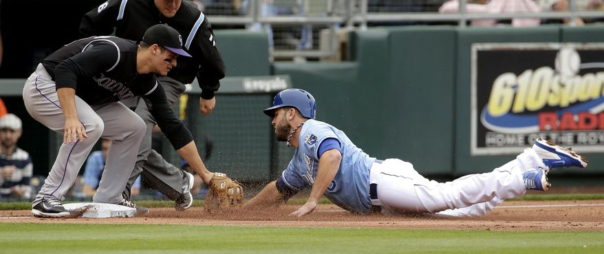 Kansas City Royals' Mike Moustakas is out at third by Colorado Rockies third baseman Nolan Arenado as he tried to steal during the second inning of a baseball game Wednesday, May 14, 2014 in Kansas City, Mo. (AP Photo/Charlie Riedel)