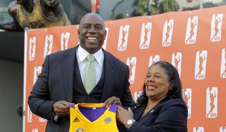 FILE - In this Feb. 5, 2014, file photo, former Los Angeles Laker Magic Johnson is joined by WNBA President Laurel Richie as they pose for photographers after a news conference in front of Staples Center in Los Angeles. Johnson is part of a group buying the Los Angeles Sparks of the WNBA. At upper left is a statue of Johnson. Richie is ready for the games to begin after a turbulent offseason. Richie faced the first major challenges of her presidency, including overseeing negotiations for a new collective bargaining agreement and the sale of the Sparks to a group headed by Johnson. (AP Photo/Nick Ut, File)