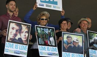 ** FILE ** Supporters of same-sex marriage hold photos of themselves and their family members or partners on the steps of the Wayne L Morse U.S. Courthouse Wednesday, May 14, 2014, in Eugene, Ore. A federal judge will hear arguments Wednesday about whether a national group can defend Oregon's ban on same-sex marriage because the state's attorney general has refused to do so. (AP Photo/The Register-Guard, Chris Pietsch)