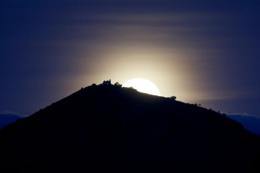 A full moon rises over a hill, Wednesday, May 14, 2014, in Tepexpan, Mexico. (AP Photo/Julio Cortez)