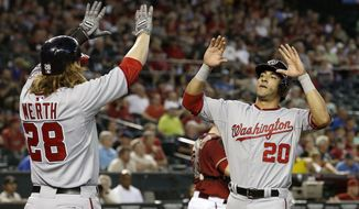 Washington Nationals' Ian Desmond (20) celebrates with Jayson Werth (28) after both scored on a single by teammate Tyler Moore during the ninth inning of a baseball game against the Arizona Diamondbacks on Wednesday, May 14, 2014, in Phoenix.  The Nationals' Desmond broke the tie in the ninth with a 2-run single and the Nationals defeated the Diamondbacks 5-1. (AP Photo)