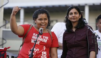File -- In this May 1, 2014 file photo, Seattle City Council Member Kshama Sawant, right, looks on as Stephanie Sucasaca holds up a fist as Sawant had just done while interpreting Sawant's remarks into Spanish at a May Day rally in support of immigrant and workers rights and a boost in the minimum wage, in Seattle. While the Seattle mayor is proposing to raise the wage to $15 in the coming years to the highest level in the nation, some activists say that's too slow and are threatening to take the issue to voters with a ballot measure that would force a raise sooner. (AP Photo/Elaine Thompson, File)