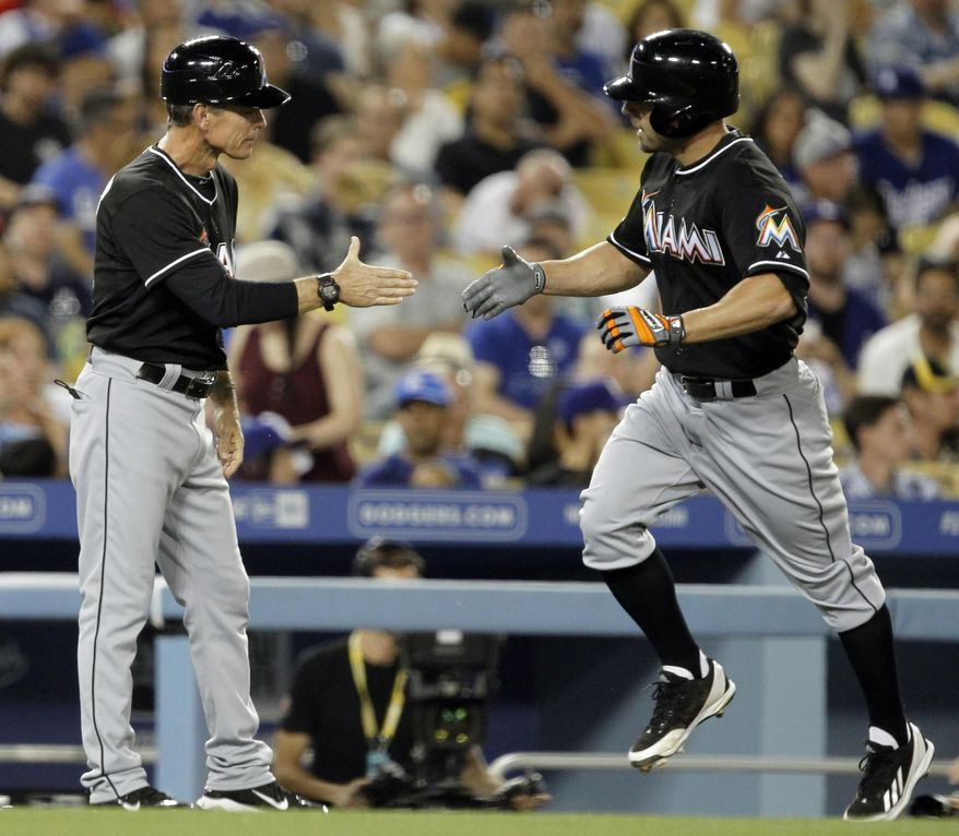 Miami Marlins third base coach Brett Butler, left, congratulates Reed Johnson on his two-run home run against the Los Angeles Dodgers in the fourth inning of a baseball game Wednesday, May 14, 2014, in Los Angeles. (AP Photo/Alex Gallardo)
