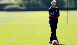 Arsenal manager Arsene Wenger,  pauses,  during a training session with his team,  in London Colney, Hertfordshire, Wednesday May 14, 2014. Arsenal are playing Hull City in the FA Cup final on Saturday. (AP Photo/PA,  David Davies) UNITED KINGDOM OUT