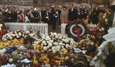 Visitors pay tribute at the flower-bedecked grave of President John Fitzgerald Kennedy at Arlington National Cemetery in November, 1963. (Associated Press)