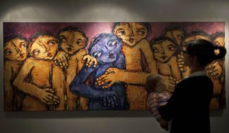 "In this photo taken Saturday, May 10, 2014, a woman carrying her child, stands in front of an oil on canvas painting named The Bitter and the Bitterness, by Palestinian artist Raouf al-Ajouri, during an art exhibition ""Traces, a testimony to memory,"" displaying over forty Palestinian artists work from Gaza, in the West Bank city of Ramallah. Fifty-three paintings and two sculptures by 45 artists have gone on display in the West Bank city of Ramallah, said Haneen Qatamesh, a spokeswoman for one of the sponsors, the Palestinian company PADICO. Since Saturday's opening, 12 works have been sold for prices ranging from $850 to $9,000, she said. (AP Photo/Nasser Nasser)"