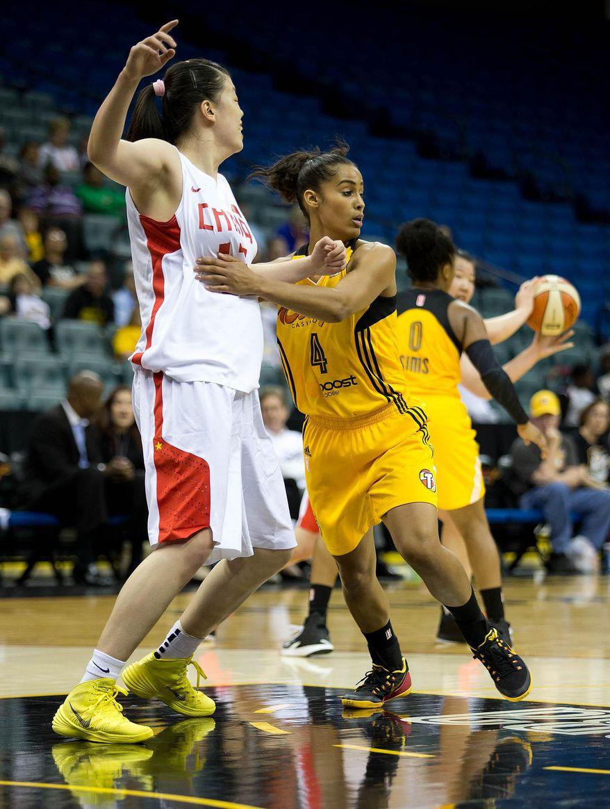 Tulsa Shock's Skylar Diggins (4) holds China's Yu Dong (13) during a WNBA basketball game on Monday, May 12, 2014, in Tulsa, Okla. (AP Photo/Tulsa World,  Joey Johnson)