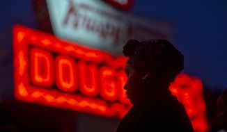Burger King employee Keisha King, 23, stands during a protest outside a Krispy Kreme store, Thursday, May 15, 2014, in Atlanta. Calling for higher pay and the right to form a union without retaliation, fast-food chain workers in Atlanta protested Thursday as part of a wave of strikes and protests in 150 cities across the U.S. and 33 additional countries on six continents. (AP Photo/David Goldman)