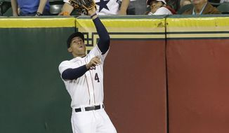 Houston Astros right fielder George Springer (4) makes the catch and the out on Texas Rangers' Mitch Moreland as the fans look on in the fifth inning of a baseball game Wednesday, May 14, 2014, in Houston. (AP Photo)