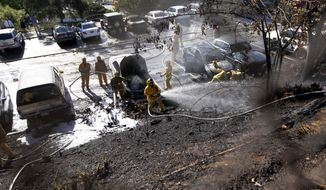 Los Angeles City firefighters extinguish flames that swept up a hillside behind a parking lot at Palisades Charter High School in the Pacific Palisades area of Los Angeles Thursday, May 15, 2014. It's believed the fire started when a student backed his car into a parking space and its exhaust pipe set off tinder-dry brush. Seven cars were damaged. No injuries were reported. (AP Photo/Reed Saxon)