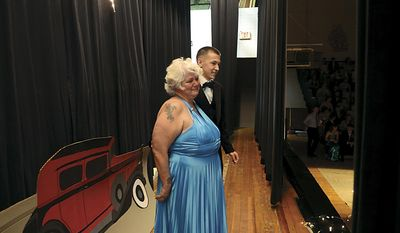In this April 25, 2014 photo, Julie Stees accompanies her 18-year-old grandson Justin in the grand march at Prophetstown High School prom in Prophetstown, Ill  What started as a bit of a joke turned into Justin asking her to be his prom date. (AP Photo/Sauk Valley Media, Alex T. Paschal)