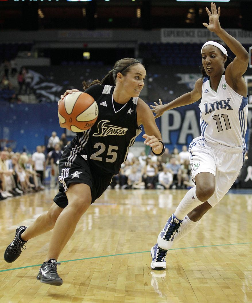 """File- This Aug. 4, 2011 file photo shows San Antonio Silver Stars guard Becky Hammon, left, driving past Minnesota Lynx guard Candice Wiggins in the first half of a WNBA basketball game in Minneapolis. Hammon's return from injury is critical to the team's fortunes. Entering her 16th season, she has career averages of 13.3 points and 3.8 assists. """"Becky makes things work,"""" coach Dan Hughes said. """"She's veteran enough to understand not only her position, but the totality of what we're doing. She can communicate it on the floor in a way that provides understanding and that's what your great players do."""" (AP Photo/Stacy Bengs, File)"""