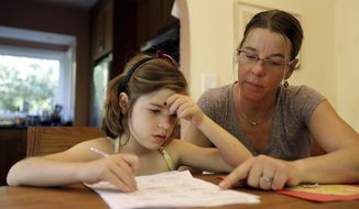Stacey Jacobson-Francis, right, works on math homework with her 6-year-old daughter Luci Wednesday, May 14, 2014, at their home in Berkeley, Calif. (AP Photo)