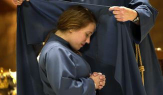 Sister Maria Lucia Stella Maris kneels on the altar at St. Pius X Roman Catholic church as Mother Mary Catherine adds the scapular to her habit May 1, 2014 in Appleton, Wis. The service established the Missionaries of the Word, which is a new religious community of women who will teach young people about Jesus. (AP Photo/The Post-Crescent, Wm. Glasheen)