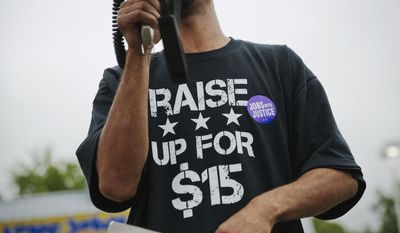 Long John Silver's employee Antwon Brown, 31, uses a bullhorn while wearing  a shirt advocating for higher wages during a protest outside a Long John Silver's restaurant, Thursday, May 15, 2014, in Atlanta. Calling for higher pay and the right to form a union without retaliation, fast-food chain workers in Atlanta protested Thursday as part of a wave of strikes and protests in 150 cities across the U.S. and 33 additional countries on six continents. (AP Photo/David Goldman)