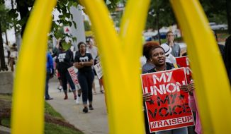 Burger King employee Brittany Buckhannon, 24, right, demonstrates during a protest for higher wages and worker's unions outside a McDonald's restaurant, Thursday, May 15, 2014, in Atlanta. Calling for higher pay and the right to form a union without retaliation, fast-food chain workers protested Thursday as part of a wave of strikes and protests in 150 cities across the U.S. and 33 additional countries on six continents. (AP Photo/David Goldman)