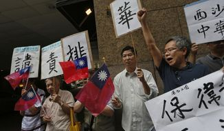 ** FILE ** Protesters raise Taiwanese flags and placards marching to Vietnam's consulate in Hong Kong, Thursday, May 15, 2014, to protest anti-China unrest in Vietnam. Mobs burned and looted scores of foreign-owned factories in Vietnam following a large protest by workers against China's recent placement of an oil rig in disputed Southeast Asian waters, officials said Wednesday. (AP Photo/Vincent Yu)