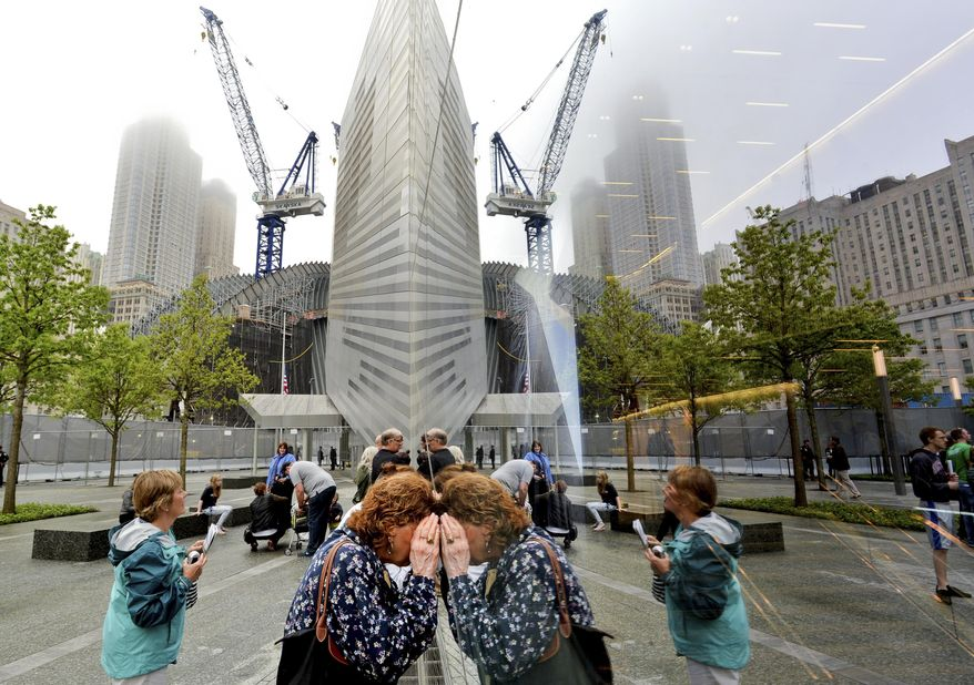 People try to look through the windows of the National September 11 Memorial Museum during the museum's dedication in New York, on Thursday, May 15, 2014. (AP Photo/EPA, Justin Lane, Pool)