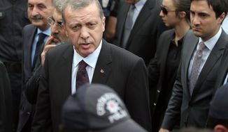 In this Wednesday, May 14, 2014, photo, Yusuf Yerkel, right, advisor to Turkish Prime Minister Recep Tayyip Erdogan, stands behind Erdogan during his visit in Soma, Turkey. Yerkel  was identified by Turkish media as the advisor who kicked a protester who was held by special forces police members during Erdogan's visit to  Soma, Turkey. Erdogan was visiting the western Turkish mining town of Soma after Turkey's worst mining accident . (AP Photo/Emrah Gurel)