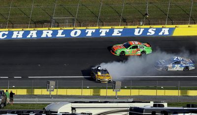 Marcos Ambrose (9) spins on the back stretch in front of Danica Patrick (10)  and Cole Whitt (26) during the NASCAR Sprint Showdown auto race at Charlotte Motor Speedway in Concord, N.C., Friday, May 16, 2014. (AP Photo/Gerry Broome)