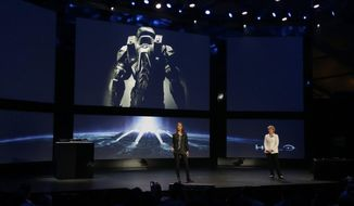 """FILE - In this May 21, 2013 file photo, Nancy Tellem, right, the entertainment and digital media president of Microsoft, and Bonnie Ross, left, general manager and studio head of 343 Industries, announce a new Halo live-action TV series for Xbox Live, during an event to unveil the next-generation Xbox One entertainment and gaming console system, in Redmond, Wash. Master Chief is returning to the battlefield next year. Microsoft announced plans Friday, May 16, 2014, to release the video game sequel """"Halo 5: Guardians"""" for the Xbox One and a """"Halo"""" television series to be produced by Steven Spielberg in fall 2015. (AP Photo/Ted S. Warren, file)"""
