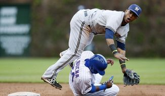 Milwaukee Brewers shortstop Jean Segura forces out Chicago Cubs' Luis Valbuena while turning a double play during the third inning of a baseball game on Friday, May 16, 2014, in Chicago. (AP Photo/Andrew A. Nelles)