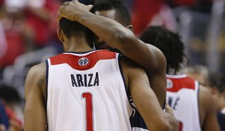 Washington Wizards forwards Trevor Ariza (1) and Martell Webster (9) hug after Game 6 of an Eastern Conference semifinal NBA basketball playoff series in Washington, Thursday, May 15, 2014. The  Indiana Pacers defeated the Wizards 93-80 to advance to the Eastern Conference finals. (AP Photo/Alex Brandon)
