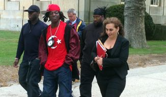 Entertainer Flavor Flav, center, walks out of Nassau County Court in Mineola, N.Y., on Friday, May 16, 2014. His attorney, Indji Bessim, right, said she is still trying to work with prosecutors to settle speeding and unlicensed driving charges against Flav, whose real name is William Drayton.  He was arrested on Long Island in January on his way to his mother's funeral. (AP Photo/Frank Eltman)