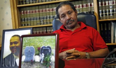 Ernesto Abreu listens during a news conference at his attorney's office in Quincy, Mass., Thursday, May 15, 2014, with photos of his son, Daniel de Abreu, and the gravesite of Daniel and Safiro Furtado. Daniel and Safiro were shot to death as they sat in a car in Boston's South End on July 16, 2012. Former New England Patriots' Aaron Hernandez, who already faces a murder charge in a man's shooting death last year, has been indicted Thursday on new murder charges in this 2012 double slaying in Boston. (AP Photo/Elise Amendola)