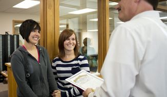 Beth Moore, left, and her partner Abby Hill, center, exchange vows in a marriage ceremony performed by Jeremy Hernandez, right, at the Washington County Courthouse in Fayetteville, Ark., Friday May 16, 2014.  The Washington County clerk has resumed issuing marriage licenses to same-sex couples, a day after a circuit judge in Pulaski County ruled that all state laws barring gay marriage are unconstitutional. (AP Photo/Sarah Bentham)