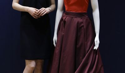 """In this Wednesday, May 14, 2014 photo, British actress Michelle Dockery, stands with her Prada gown that she wore to the 2013 Emmy's, at Christie's auction rooms in London. """"Downton Abbey"""" star Michelle Dockery is selling the eye-catching gown she wore to last year's Emmy Awards to help victims of the Syria civil war. Christie's auction house says the Prada dress, featuring a red halter-style top and burgundy skirt, will go under the hammer in London on June 20. Proceeds will go to humanitarian organization Oxfam. The gown is expected to fetch between 3,000 pounds and 5,000 pounds ($5,000 and $8,400). The actress, who plays Lady Mary in the costume drama, visited a Syrian refugee camp in Jordan last year. (AP Photo/Kirsty Wigglesworth)"""