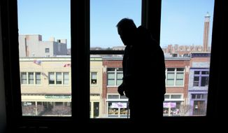 ADVANCE FOR RELEASE SUNDAY, MAY 18, 2014, AT 12:01 A.M. EDT - In this May 6, 2014 photo, Dave Witt looks out a window facing Huron Avenue at the lofts above Ben's Fine Furniture in downtown Port Huron, Mich. The Witts' Port Huron loft total will reach 43 upon completion, he told the Times Herald of Port Huron. The Witts have completed six other loft renovation projects, the majority in downtown Port Huron, and including the construction of the Arashi Lofts just north of the Military Street Bridge. (AP Photo/The Port Huron Times Herald, Jeffrey Smith)  NO SALES