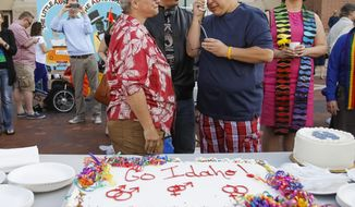 CORRECTS NAME FROM JUDY MAY-CHANG TO JODY MAY-CHANG Maria May-Chang, right, wipes away a tear after having a piece of cake with her wife Judy May-Chang, left,  and their son Cody  at the Ada County Courthouse in Boise, Idaho, on Friday, May 16, 2014. Maria and Jody were married last year in Washington state and were hoping to get a license in Idaho after a federal judge overturned Idaho's gay marriage ban on Monday, ordering the state to issue marriage licenses to same sex couples beginning Friday morning.  On May 15, 2014, the 9th U.S. Circuit Court of Appeals gave Idaho a temporary stay from that order.  (AP Photo/Otto Kitsinger)