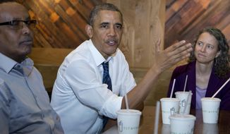 President Barack Obama flanked by Abdullahi Mohamed, left, and Meredith Upchurch speaks to reporters at a restaurant in Washington, Friday, May 16, 2014.  The president and Vice President Joe Biden met with construction workers involved in a recent infrastructure project.   (AP Photo/Manuel Balce Ceneta)