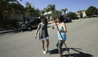 Nina Huang, left, greets her neighbor, Snow Teng, right, in the middle of their street after coming home from wildfire evacuations Friday, May 16, 2014, in Carlsbad, Calif.  Some evacuation orders were lifted early Friday in an area near the fiercest of several wildfires in San Diego County, as crews building containment lines around the blazes hoped cooler temperatures will help them make further progress. (AP Photo/Gregory Bull)