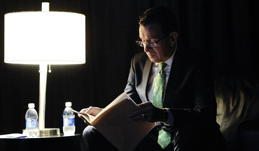 Gov. Dannel P. Malloy reads over his speech in a private area backstage while waiting as delegates nominate him as the Democratic candidate for governor at the Connecticut Democratic Convention, Friday, May 16, 2014, in Hartford, Conn. (AP Photo/Jessica Hill)