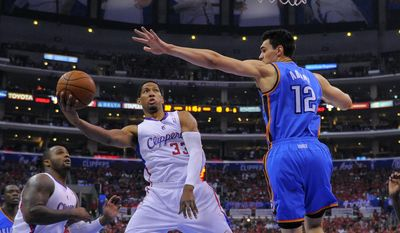 Los Angeles Clippers forward Danny Granger, center, puts up a shot as Oklahoma City Thunder center Steven Adams, right, of New Zealand, defends and forward Glen Davis looks on in the first half of Game 6 of the Western Conference semifinal NBA basketball playoff series, Thursday, May 15, 2014, in Los Angeles. (AP Photo/Mark J. Terrill)