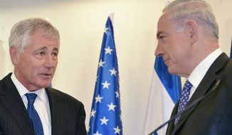 Israeli Prime Minister Benjamin Netanyahu, right, shakes hands with U.S. Defense Secretary Chuck Hagel while delivering remarks at his office on Friday, May 16, 2014 in Jerusalem. (AP Photo/Mandel Ngan, Pool)