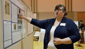 In this April 22, 2014 photo, Jennifer Wegmann-Gabb, a post-baccalaureate student at Northern Illinois University in DeKalb, Ill., talks about the 13th century Paris Bible leaf she spent weeks researching. Wegmann-Gabb presented her research during Undergraduate Research and Artistry Day at the university. (AP Photo/Daily Chronicle, Monica Maschak)