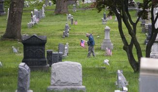 ** FILE ** Veteran Randall Adams walks through the Shamokin Cemetery in Shamokin, Pa., while placing U.S. flags on the tombstones of veterans Friday, May 16, 2014. He and other members of American Legion Post 73, Shamokin, and other volunteers placed the flags in preparation of Memorial Day. (AP Photo/The News-Item, Larry Deklinski)
