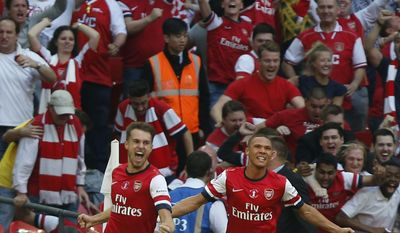 Arsenal's Aaron Ramsey, left, celebrates his goal against Hull City with teammate Kieran Gibbs during their English FA Cup final soccer match at Wembley Stadium in London, Saturday, May 17, 2014. (AP Photo/Sang Tan)
