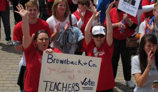 Pittsburg, Kan., teachers Salli Chowning, front left, and Regina Winemiller, front center, in the white cap, protest with other educators and supporters of public schools, Saturday, May 17,. 2014, at the Statehouse in Topeka, Kan. Participants question Republican Gov. Sam Brownback's commitment to public schools. (AP Photo/John Hanna)