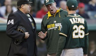 Oakland Athletics manager Bob Melvin, center, argues with home plate umpire Jerry Layne as starting pitcher Scott Kazmir listens during the second inning of a baseball game against the Cleveland Indians, Saturday, May 17, 2014, in Cleveland. Kazmir was ejected from the game. (AP Photo/Tony Dejak)