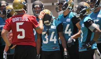 Newly drafted Jacksonville Jaguars quarterback Blake Bortles (5) puts his hand on running back Storm Johnson in a huddle during the NFL football team's rookie minicamp Friday, May 16, 2014, in Jacksonville, Fla. (AP Photo/The Florida Times-Union, Will Dickey)