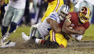 FILE - In this Dec. 30, 2012 file photo, Dallas Cowboys outside linebacker Anthony Spencer sacks Washington Redskins quarterback Robert Griffin III, right, during the second half of an NFL football game in Landover, Md. Spencer signed his third straight one-year deal with Dallas after missing all but one game last year and having two knee surgeries about a month apart. (AP Photo/Evan Vucci, File)