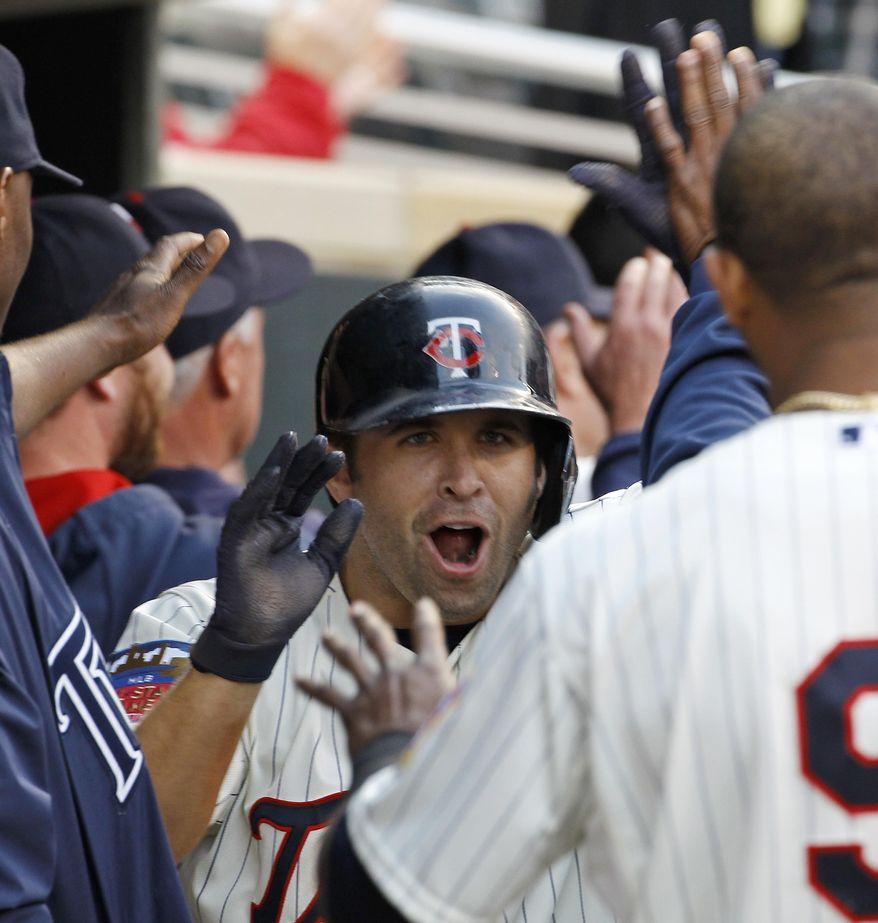 Minnesota Twins' Brian Dozier is congratulated in the dugout after hitting a three-run home run off Seattle Mariners starting pitcher Roenis Elias during the fifth inning of a baseball game in Minneapolis, Saturday, May 17, 2014. (AP Photo/Ann Heisenfelt)