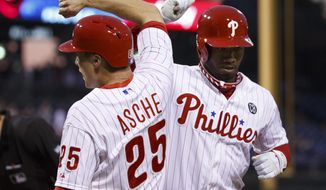 Philadelphia Phillies' Domonic Brown, right, celebrates his two-run homer with Cody Asche during the fourth inning of a baseball game against the Cincinnati Reds, Saturday, May 17, 2014, in Philadelphia. (AP Photo/Chris Szagola)