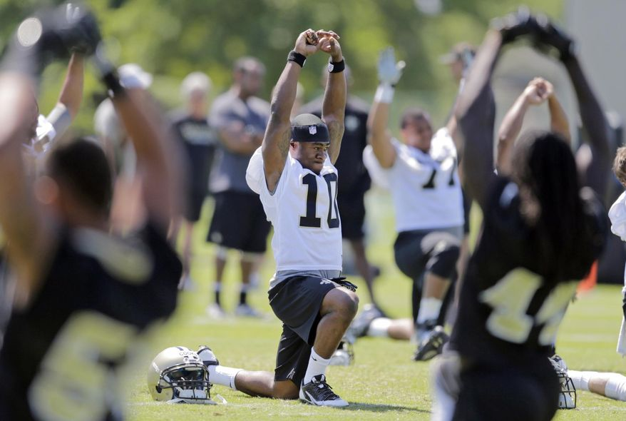 New Orleans Saints first-round draft pick wide receiver Brandin Cooks, center, warms up during NFL football rookie camp, Saturday, May 17, 2014, in Metairie, La. (AP Photo/Nola.com The Times-Picayune, Brett Duke) MAGS OUT; NO SALES; USA TODAY OUT; THE BATON ROUGE ADVOCATE OUT.