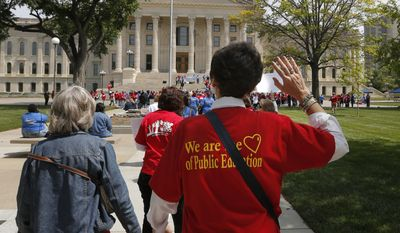 Public education supporters raise their hands as they march to the Kansas Statehouse in Topeka, Kan., Saturday, May 17, 2014. Advocates argue that the state is still not spending enough money on its public schools. (AP Photo/Orlin Wagner)